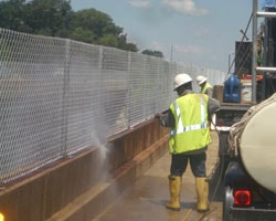 Power Washing the Concrete Wall Preparing for New Bridge Fence
