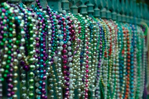 mardis gras beads on a wrought iron fence
